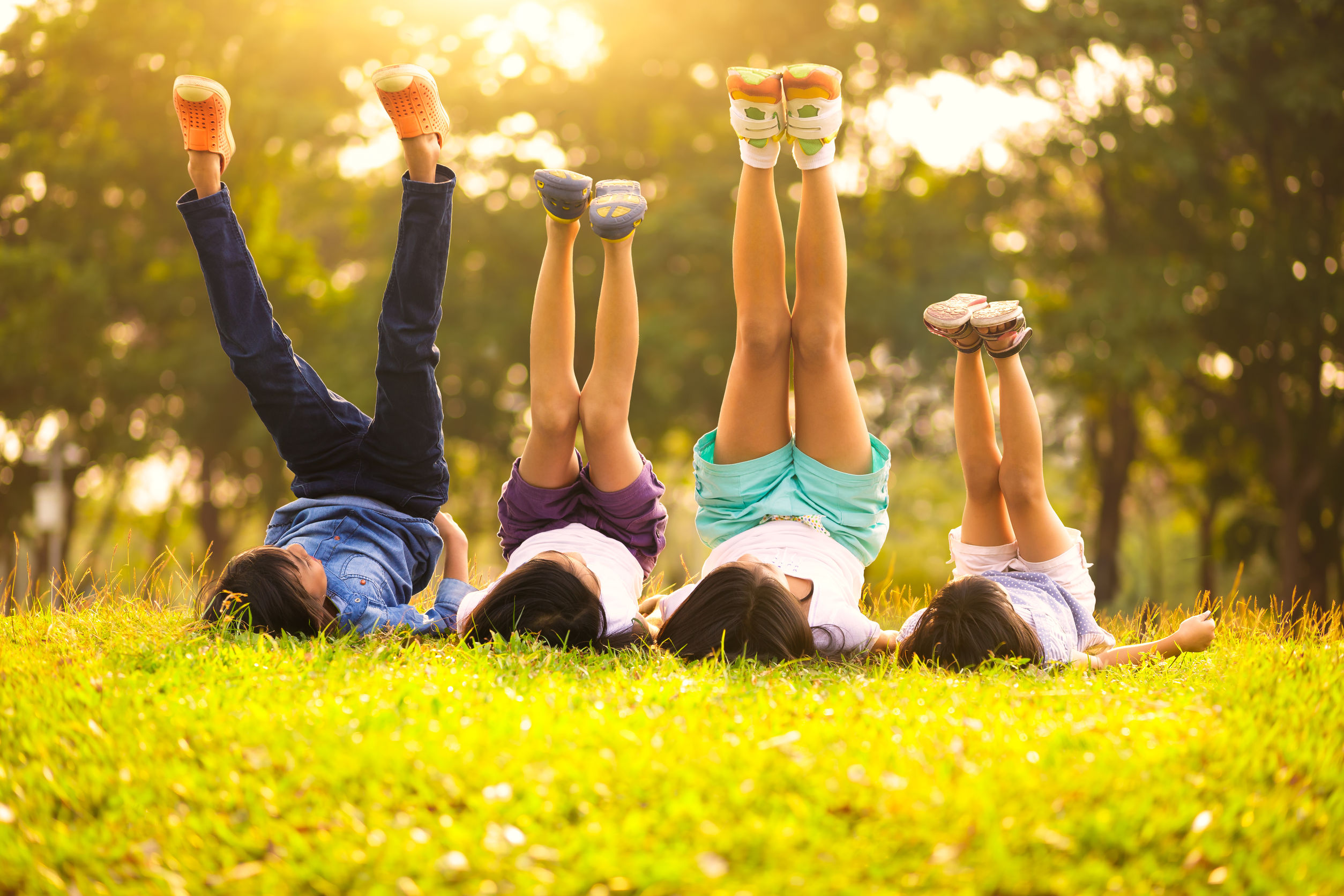 39436758 - group of happy children lying on green grass outdoors in spring park
